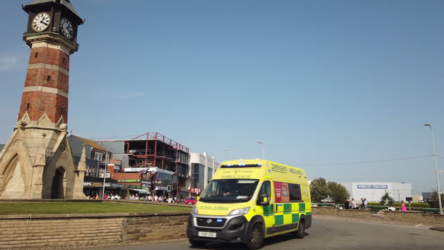 an emergancy ambulance with lights flashing turns round the clock tower roundabout in skegness lincolnshre england. - lincolnshire stock videos & royalty-free footage
