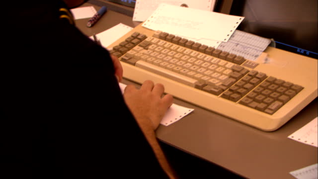 an emergency operations employee types on a keyboard and fills out forms as he takes calls. - input device stock videos & royalty-free footage