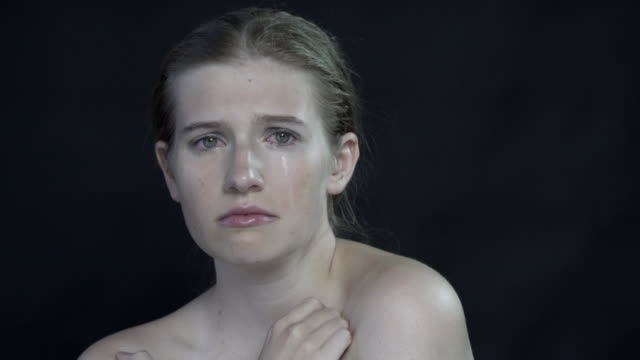 an emotional young woman crying. - distressed stock-videos und b-roll-filmmaterial