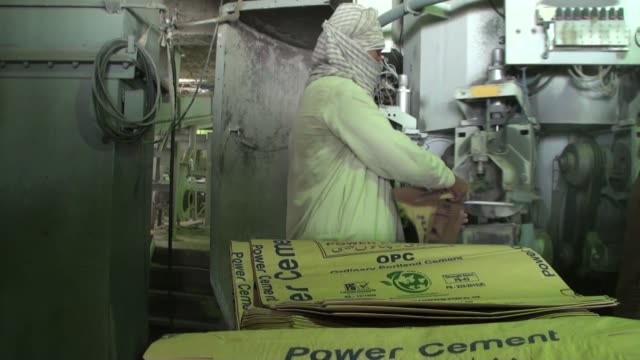 an employee adds empty sacks to a machine for filling at the power cement ltd plant operated by arif habib group in nooriabad sindh pakistan on... - sindh pakistan stock videos and b-roll footage