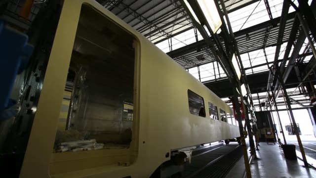 an employee applies tape to a window aperture during the manufacture of a frecciarossa 1000 high-speed train carriage during manufacture at... - treno ad alta velocità video stock e b–roll