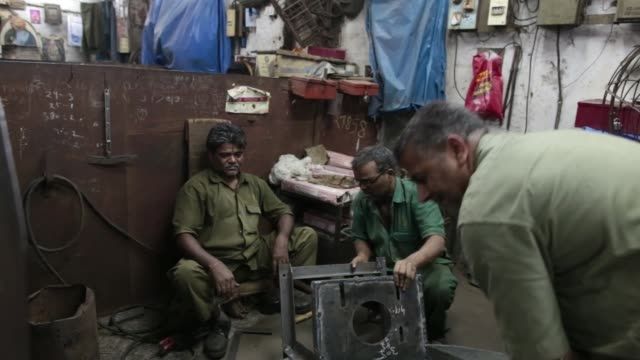 an employee arc welds a heating, pumping and filtering unit inside an ishwar engineering co. factory in mumbai, maharashtra, india, on saturday, feb.... - indian subcontinent ethnicity stock videos & royalty-free footage