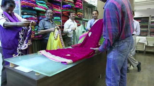 an employee arranges a dress on a clothes rail at the roopmilan store a fabric retailer operated by roopam roopmilan that supplies bridal sarees in... - sari stock videos and b-roll footage