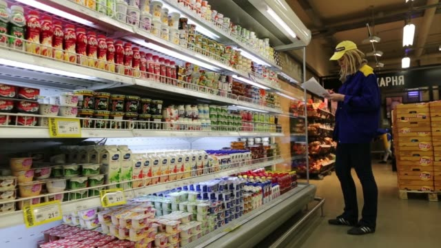 an employee arranges cartons of juice on shelves inside a lenta ltd supermarket in moscow russia on tuesday feb 26 an employee works in bakery... - display cabinet stock videos & royalty-free footage