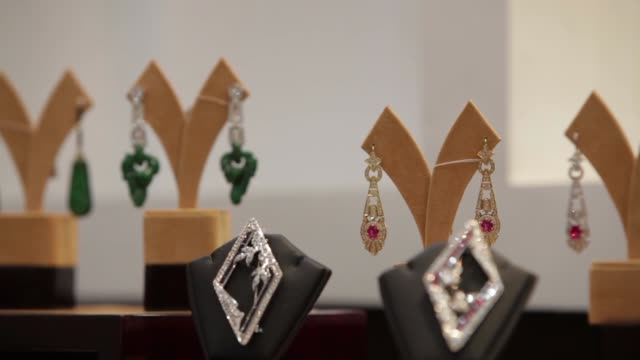 vídeos de stock e filmes b-roll de an employee arranges jewelry items on display at the myanmar ves joint venture co gems and jewelry showroom in yangon brooches sit on display in... - jade gema
