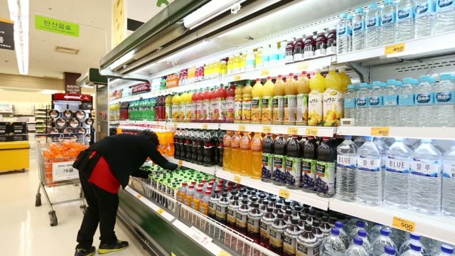 stockvideo's en b-roll-footage met an employee arranges packages of milk at an emart co store a subsidiary of shinsegae co in incheon south korea on saturday dec 21 a woman shopper... - incheon