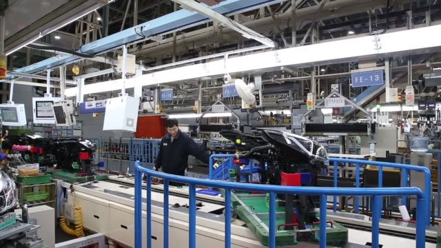 an employee assembles a vehicle chassis part and an automated guided vehicle transports the module at the hyundai mobis co factory in asan south... - fahrgestell stock-videos und b-roll-filmmaterial