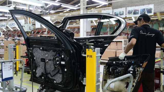 An employee assembles the chassis of a BMW AG 7Series sedan at the assembly line of a PT Gaya Motor factory in Jakarta Indonesia on Wednesday Nov 30...