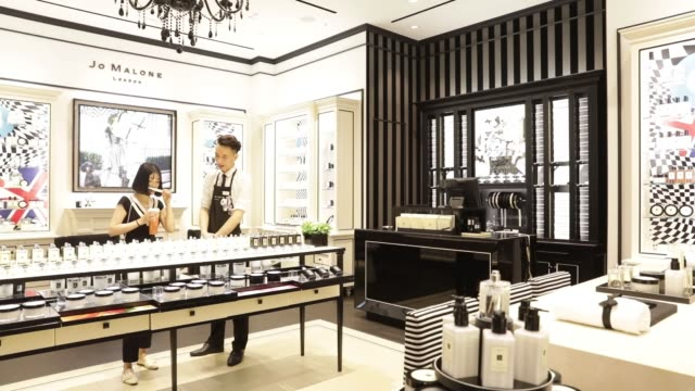 an employee assists a customer at a jo malone ltd. store in the raffles city shopping mall in shanghai, china, on wednesday, may 31 an employee... - raffles city stock videos & royalty-free footage