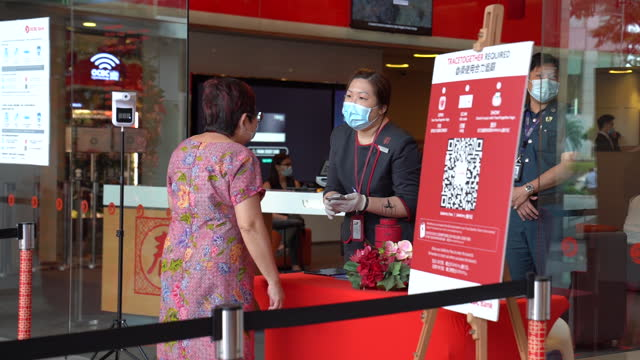 an employee assists a customer near signage for the tracetogether contact-tracing phone app at an entrance to the oversea-chinese banking corp.... - singapore stock videos & royalty-free footage