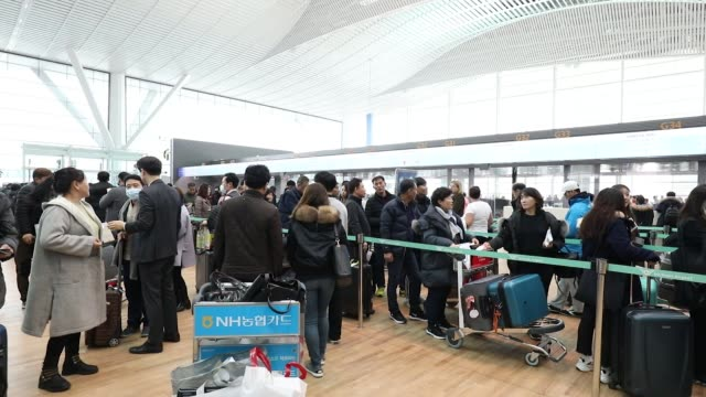 An employee assists travellers as they use self checkin kiosks inside the terminal 2 building at Incheon International Airport in Incheon South Korea...