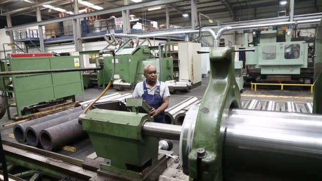 An employee attaches a drill wear sleeve to a machine during the manufacture of drilling machinery at the Bulroc UK Ltd production plant in...