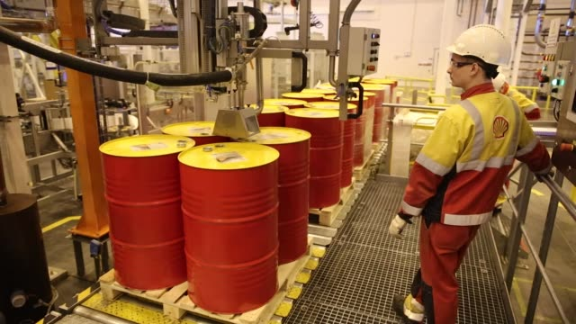 An employee caps oil drums containing lubricant oil at the Royal Dutch Shell Plc lubricants blending plant in Torzhok Russia on Wednesday Feb 7...