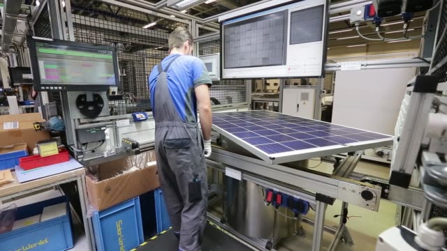 An employee carries out quality control checks on a photovoltaic module following manufacture at Solarworld AG in Freiberg Germany on Thursday July...