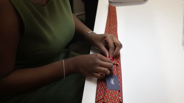 An employee carries out quality control checks on a silk tie at Drakes factory outlet store in London UK on Friday June 26 2015 Shots An employee...