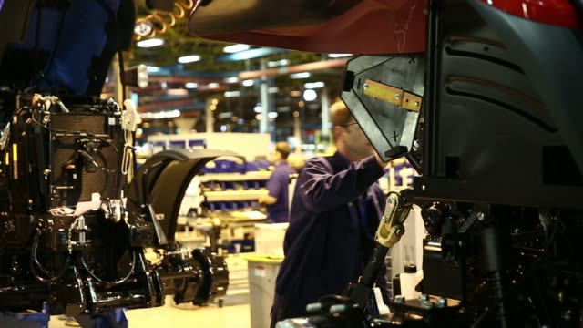 an employee checks a new holland tractor as it moves along the production line at cnh industrial nvs assembly plant in basildon, uk, on wednesday,... - basildon stock-videos und b-roll-filmmaterial