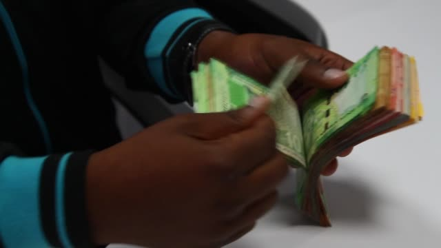 an employee counts a bundle of mixed denomination rand currency banknotes at the forex department inside a first national bank branch in... - ハウテング州点の映像素材/bロール