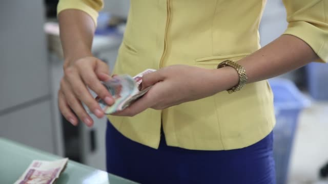 An employee counts a bundle of Myanmar one thousand Kyat banknotes at a CoOperative Bank Ltd branch in Yangon Myanmar on Thursday Oct 8 An employee...