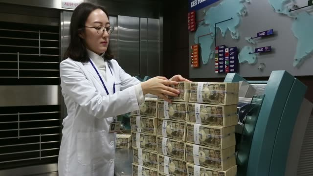 an employee counts japanese 10000 yen banknotes beyond stacks of banknotes at the korea exchange bank headquarters in seoul south korea on thursday... - 紙幣点の映像素材/bロール