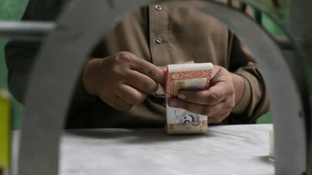An employee counts Pakistani five thousand rupee banknotes at a cash counter of the office of Pakistan Currency Exchange Pvt in Karachi Pakistan on...