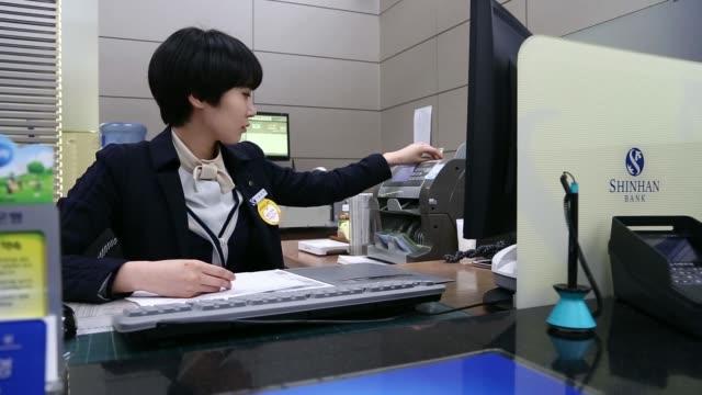 an employee counts south korean 10000 won banknotes at the shinhan bank headquarters a unit of shinhan financial group co in seoul south korea on... - 金融関係施設点の映像素材/bロール