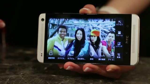 An employee demonstrates a retouch function on an image taken with the 'HTC Zoe' camera feature of the HTC Corp HTC J One HTL22 smartphone during the...
