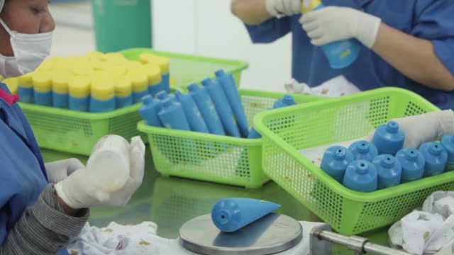 an employee fills a tube of vv vera co one all sporty shower gel employees wipe and add a cap to the top of a tube of vv vera co one all sporty... - plastic cap stock videos & royalty-free footage