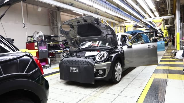 an employee fits a wheel to a mini automobile produced by bayerische motoren werke ag inside the final assembly plant in oxford uk on tuesday sept 20... - 自動車ブランド mini点の映像素材/bロール