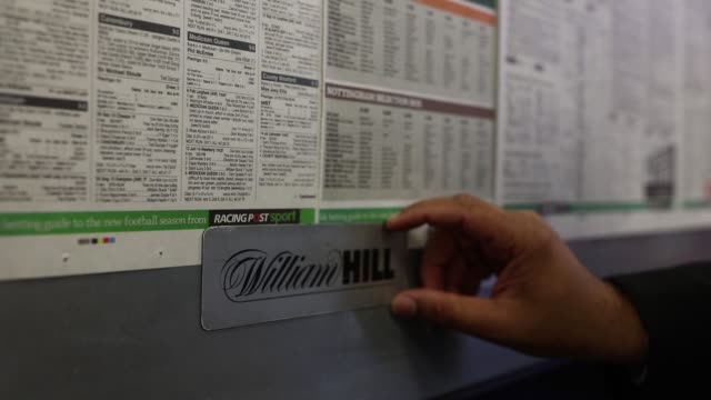 vídeos y material grabado en eventos de stock de an employee fixes a copy of the racing post newspaper horse racing guide to a wall at a william hill plc bookmakers in london uk on aug 2horse racing... - apuestas deportivas