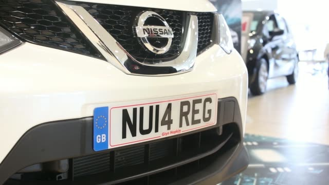 stockvideo's en b-roll-footage met an employee fixes a new 2014 vehicle license registration plate to the bumper of a nissan micra automobile produced by nissan motor co in an arranged... - bumper