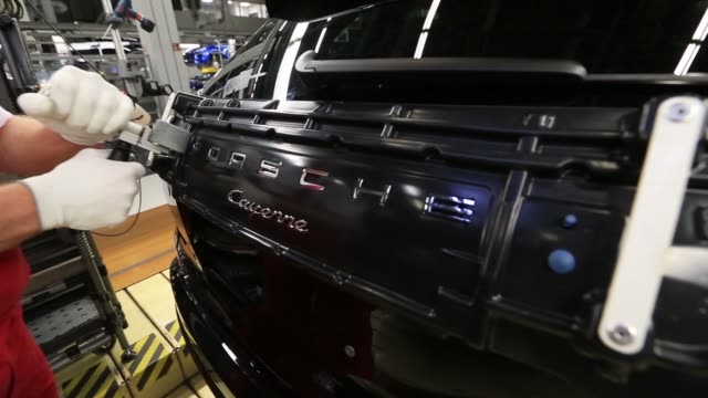 an employee fixes signage to a porsche panamera luxury automobile assembly line inside the porsche leipzig gmbh factory a unit of porsche ag in... - nordeuropäischer abstammung stock-videos und b-roll-filmmaterial