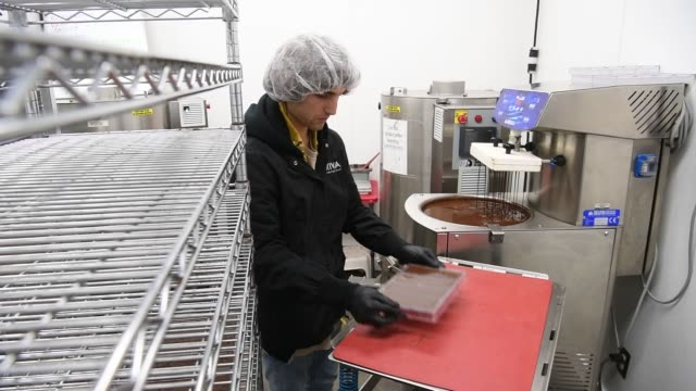 an employee for kiva confections inspects cannabisinfused chocolate bars after being poured into a tray at the company's headquarters in oakland... - kivas stock videos & royalty-free footage