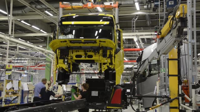 An employee guides a truck cabin along the assembly line during production at the Volvo AB manufacturing plant in Gothenburg / Employees work on the...