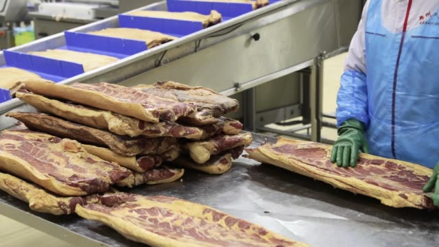 An employee handles imported a Smithfield Foods Inc pork belly on a production line that processes the pork into bacon at the WH Group Ltd facility...