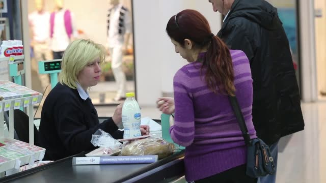 an employee hands cash to a customer at a checkout desk inside a carrefour sa supermarket part of the marinopoulos group at the mall of cyprus in... - キプロス ニコシア点の映像素材/bロール