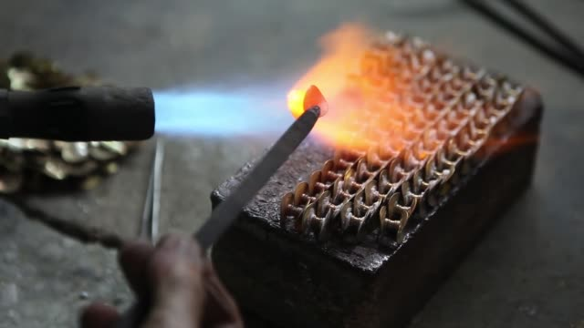 an employee heats a component of a brass instrument in the assembly department of the nadir ali co factory operated by nadir ali wind instruments pvt... - wind instrument stock videos & royalty-free footage