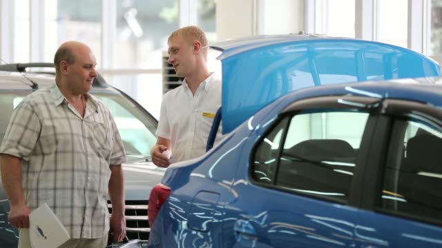vídeos y material grabado en eventos de stock de an employee helps a customer next to a line of new renault automobiles for sale inside the mosrentservis auto dealership for renault sa in moscow... - sala de muestras