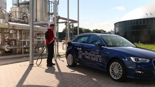 an employee holds a pump as an audi a3 gtron automobile is refueled with egas at audi ag's powertogas plant which uses electricity from wind turbines... - refuelling stock videos & royalty-free footage