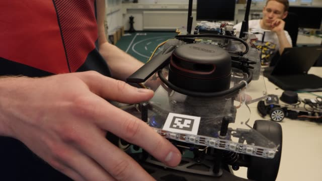 An employee holds and explains a working model of a driverless vehicle at the Dahlem Center for Machine Learning and Robotics at the Freie...