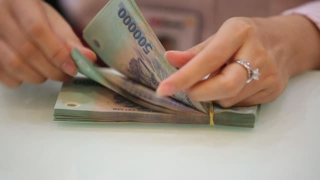 an employee holds vietnamese dong banknotes for an arranged photograph inside a ho chi minh city housing development commercial joint stock bank... - vietnam meridionale video stock e b–roll