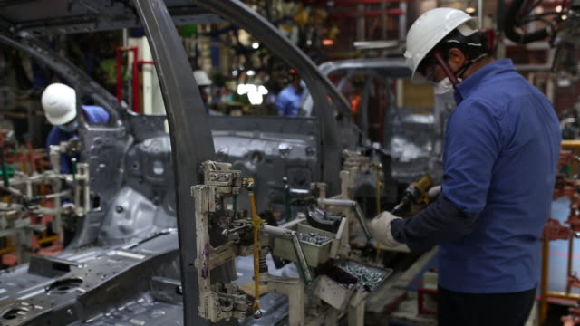 an employee in face mask and hardhat works at the toyota factory in bangalore, tamil nadu, india on tuesday, september 8, 2020. - car plant stock videos & royalty-free footage