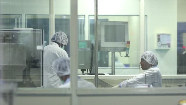 An employee in protective clothing works in the formulation room of the research and development center at the Biocon Ltd campus in Bengaluru India...