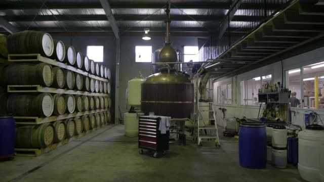 an employee inspects the level of distilled whisky in a still at the sullivans cove whisky distillery in hobart tasmania australia on thursday nov 11... - distillery still stock videos & royalty-free footage