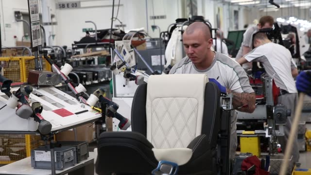 an employee irons creases from the material of seat destined for a bentley automobile as he works in the upholstery department at the bentley motors... - cheshire england stock videos & royalty-free footage