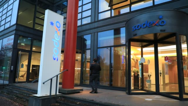 an employee leaves the sodexo head office on october 28, 2020 in issy-les-moulineaux, france. the catering giant plans to cut more than 2,000 jobs in... - entrance sign stock videos & royalty-free footage