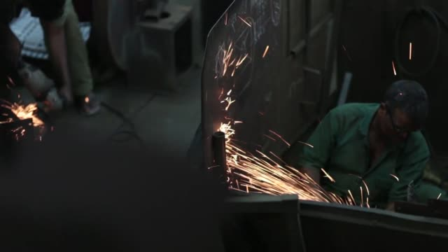an employee, left, uses an angle grinder inside an ishwar engineering co. factory in mumbai, maharashtra, india, on saturday, feb. 7 an employee uses... - indian subcontinent ethnicity stock videos & royalty-free footage