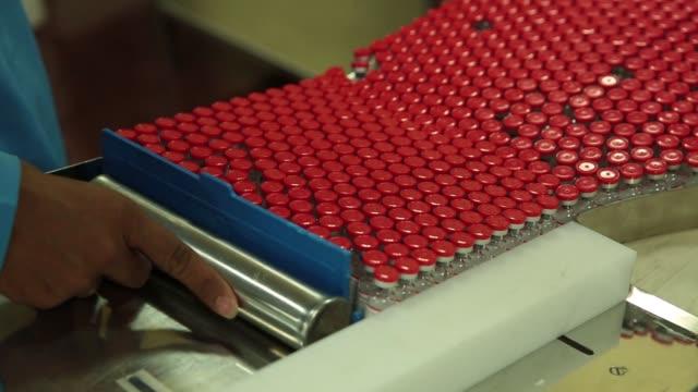 stockvideo's en b-roll-footage met an employee loads labeled vaccine vials onto a vaccine vial monitor labeling machine - medicijnflesje