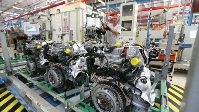 vídeos de stock e filmes b-roll de an employee lowers a completed petrol engine on to racking at the renault dacia factory in pitesti romania on thursday july 3 an employee uses a tool... - baixar