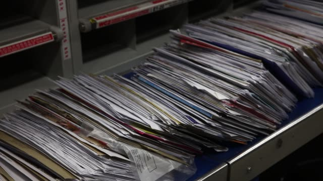 an employee manually sorts letters for delivery at the mount pleasant post sorting office, operated by royal mail plc, in london, u.k., on wednesday,... - ロイヤルメール点の映像素材/bロール