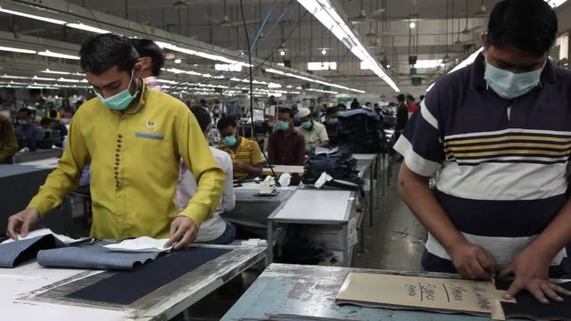 stockvideo's en b-roll-footage met an employee marks on a denim fabric in the stitching unit of the artistic denim mills ltd factory in karachi pakistan on tuesday feb 6 employees... - spijkerstof